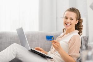パソコンをしながらクレジットカードを持つ女性