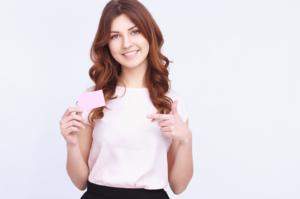 右手に持っているカードを指差す女性