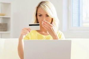 クレジットカードを見つめて口をふさぐ女性