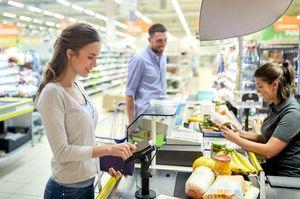 スーパーマーケットのレジで支払う女性