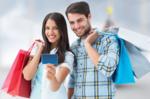 カードを持つ女性と一緒に買い物する男性