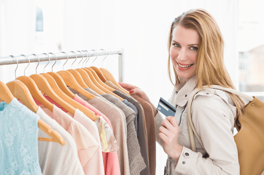 洋服店でカードを持って買い物する女性