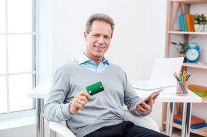 タブレットをしながらカードを持つ男性