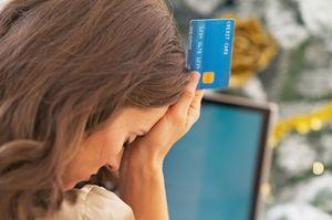 クレジットカードを持ちながらへこむ女性