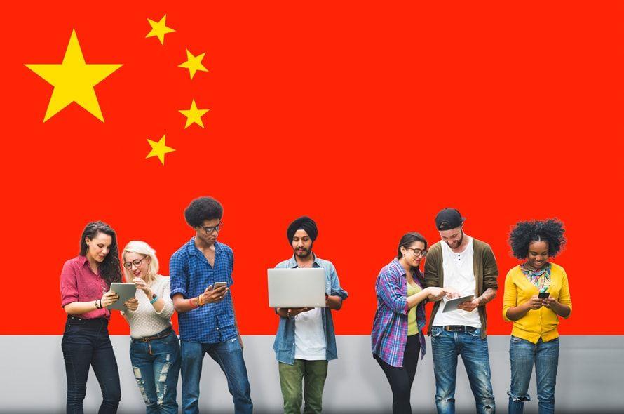 中国国旗の後ろに並ぶ人々