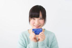 両手でクレジットカードを持つ女性
