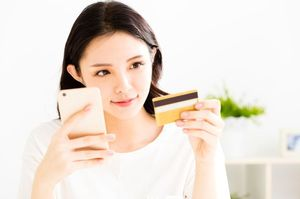 スマホを見ながらカードを持つ女性