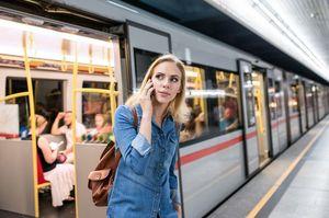 電車のホームで電話する女性