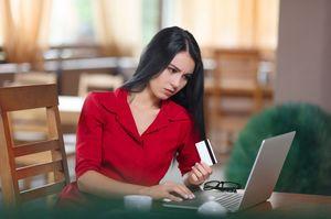 カードを持ちながらパソコンをする女性