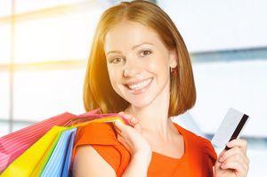 買い物袋を持ちながらカードを持つ女性