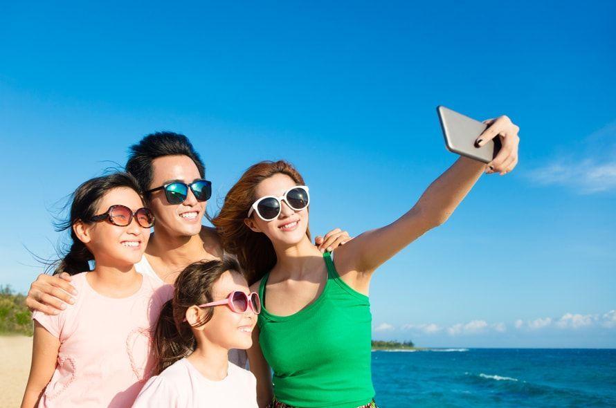 海で写真をとる家族