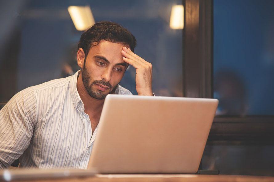 困った顔でパソコンを見る男性