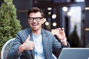 親指を立てて喜びながらゴールドカードを持つ男性