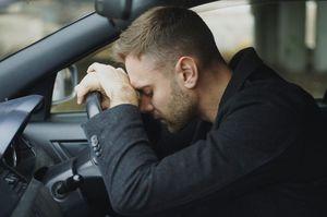 車の中で塞ぎこむ男性
