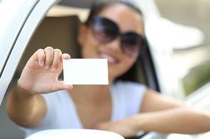 車の中からカードを見せる女性