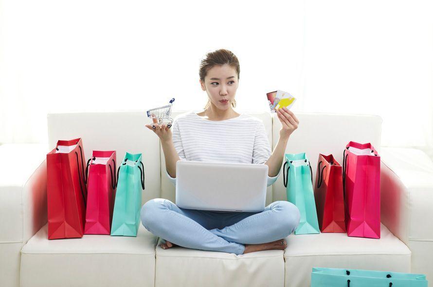 買い物袋を並べてカードを見る女性