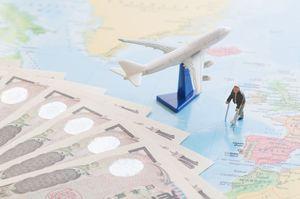 世界地図の上にお札と飛行機と杖をついた人の模型