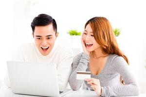 パソコン見ながら笑う男性とクレジットカードを持ちながら笑う女性