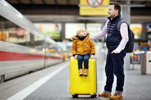 電車のホームでキャリーに乗っている子供とその父親