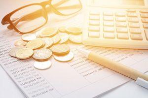 机の上にある電卓とめがねとコイン