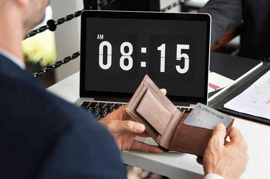 パソコンに表示される時間を見ながらカードを触る男性