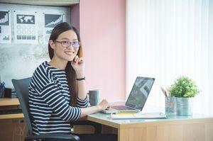 机でパソコンを触る女性