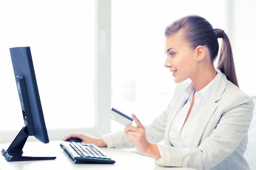 デスクでパソコンを見ながらカードを持つ女性