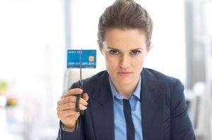 はさみでクレジットカードを切ろうとする女性
