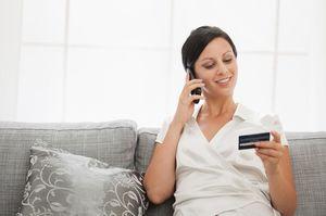 ソファーで電話しながらカードを持つ女性