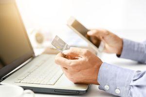 クレジットカードを見ながらスマホをPCを触る会社員