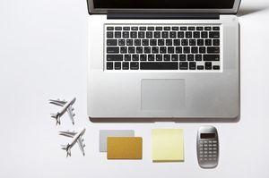 パソコンの近くにある2つの飛行機の模型とカードと付箋と電卓