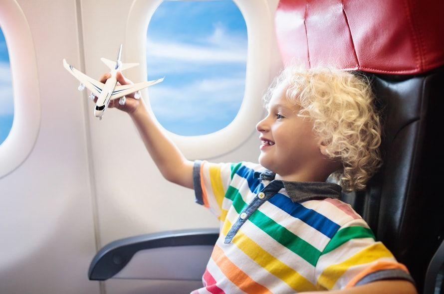 機内で飛行機の模型を飛ばして遊ぶ男の子