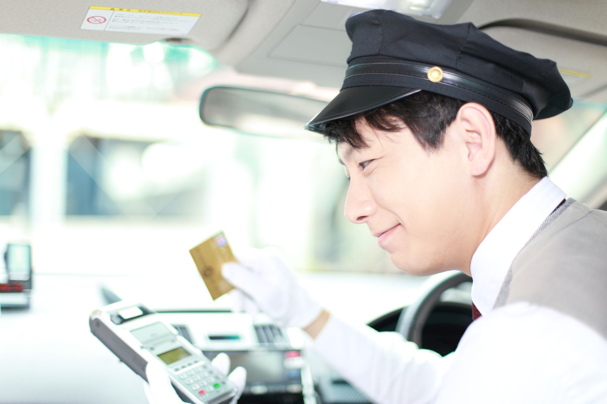 タクシーでカード決済をする男性