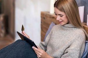 カードとタブレットを操作する女性
