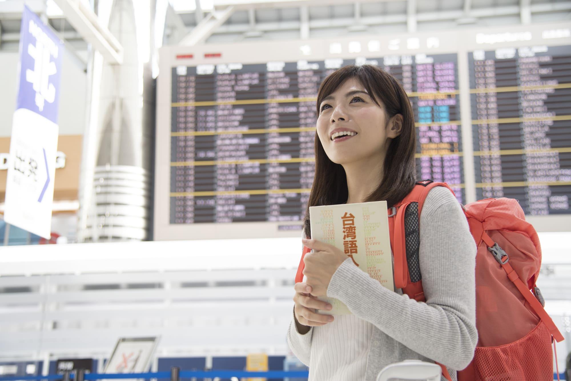 空港でリュックを背負い微笑む女性