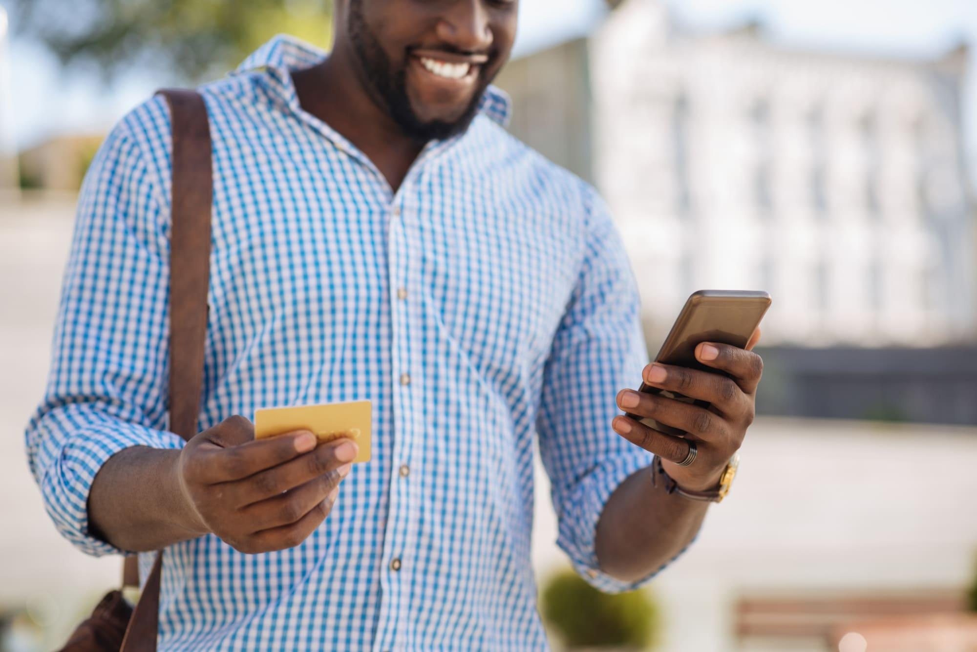 スマホとクレジットカードを見ながら微笑む外国人男性