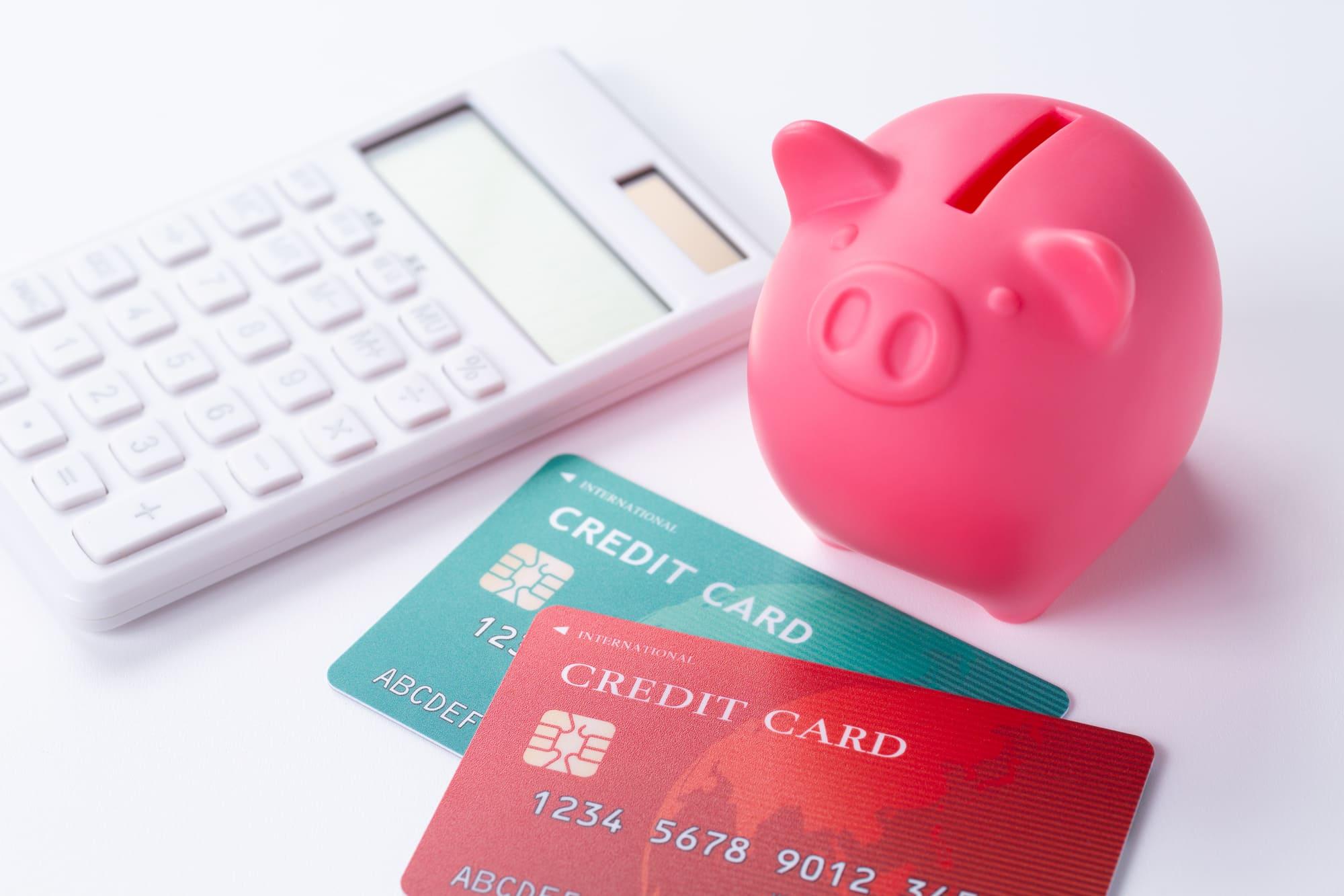 ピンクの豚の貯金箱とクレジットカード2枚