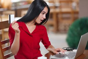 クレジットカードの情報をパソコンから見る女性