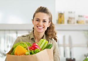 食料品をキッチンで抱える女性