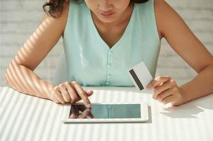 タブレットを触りながらカードを持つ女性
