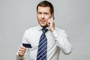 電話をしながらカードを持つ男性