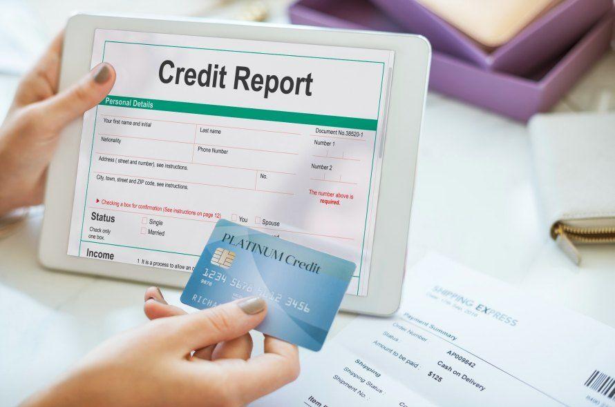 Credit Reportと表示されたタブレットとカードを持つ人
