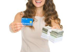 クレジットカードと現金を見せる女性