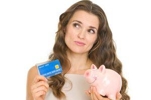 貯金箱を持ちながらクレジットカードを見せる女性