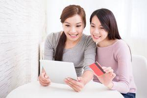 タブレットとクレジットカードを持つ女性達