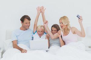 パソコンを見る家族とクレジットカードを持つ女性
