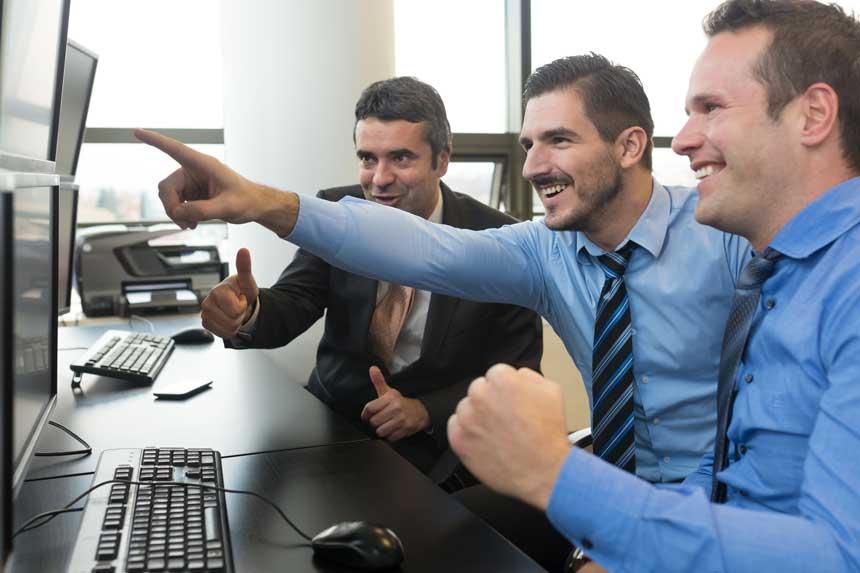 パソコン画面を見ながら喜ぶ3人のビジネスマン