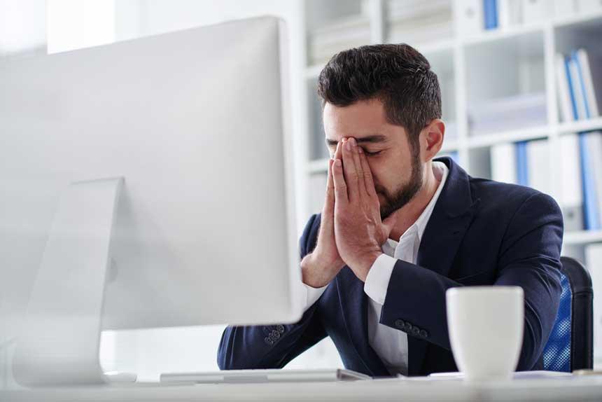 パソコン画面の前でうなだれる男性