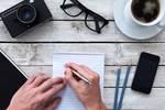 デスクで勉強する男性の手と文房具とコーヒー