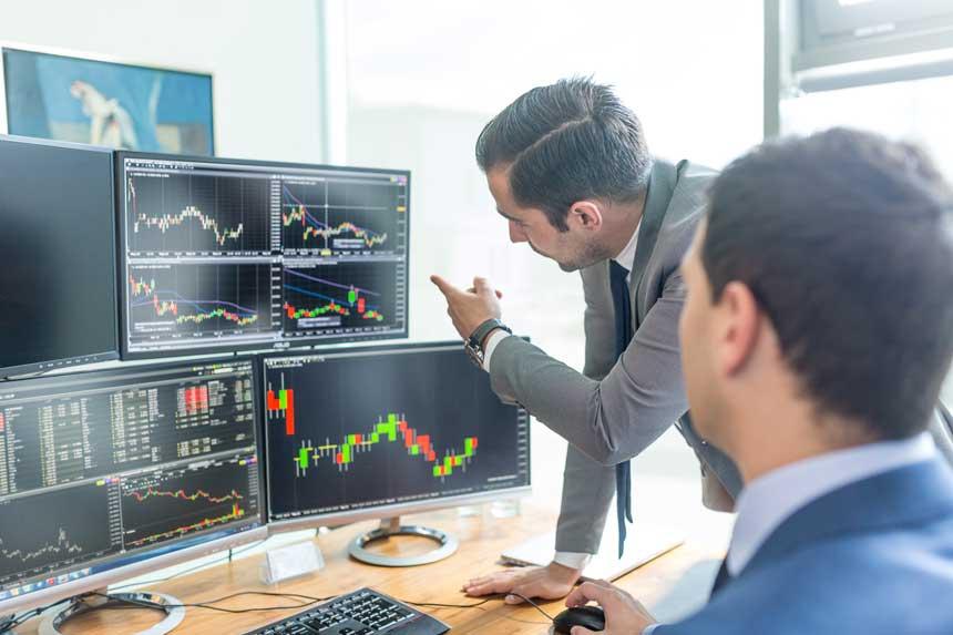 4つのモニターに映し出されたチャートを指差す男性とそれを見ながらPCを操作する男性